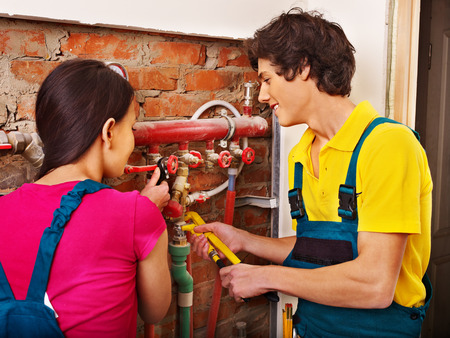 heat pump: Men builder fixing heating system with special tool.