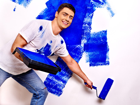 painting and decorating: Happy man paint wall at home.