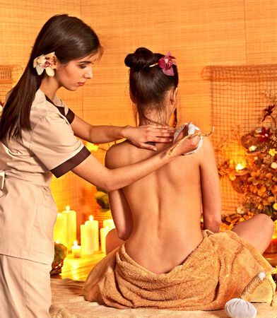 herbal massage ball: Young woman getting thai herbal massage ball