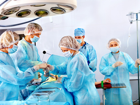 surgical coat: Team surgeon at work in operating room.