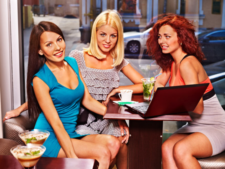 Two women at laptop drinking cocktail in a cafe. photo