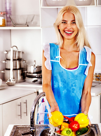 Happy woman washing fruit at kitchen. photo