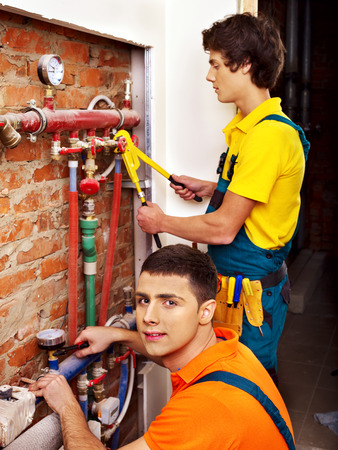 electrical appliances: Men builder fixing heating system with special tool.