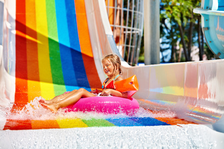 aquapark: Happy child girl in yellow bikini sliding water park.