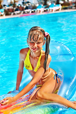 Little girl swimming on inflatable beach mattress. Stock Photo