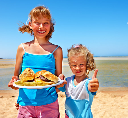 high calorie foods: Child eating fast food at beach outdoor.