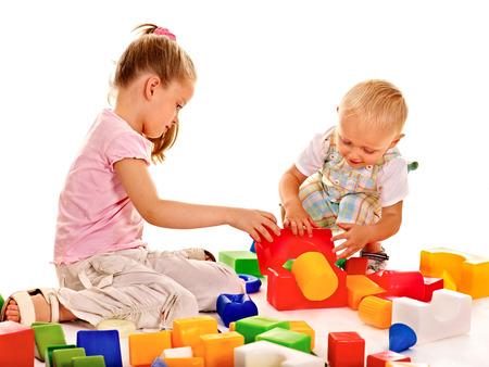 hermanos jugando: Niños felices que juegan bloques de edificio aislado