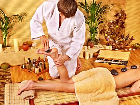 Woman getting feet massage. Male therapist. photo