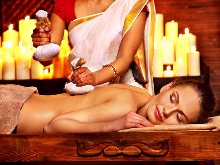 ayurvedic: Woman having ayurvedic massage with pouch of rice.