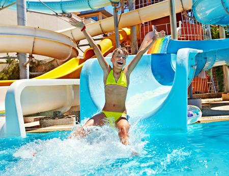 Happy child girl in bikini sliding water park. Standard-Bild
