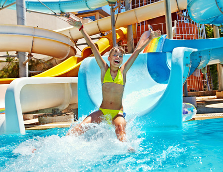 Happy child girl in bikini sliding water park. Stock Photo