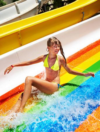 Happy child girl in bikini sliding water park. photo