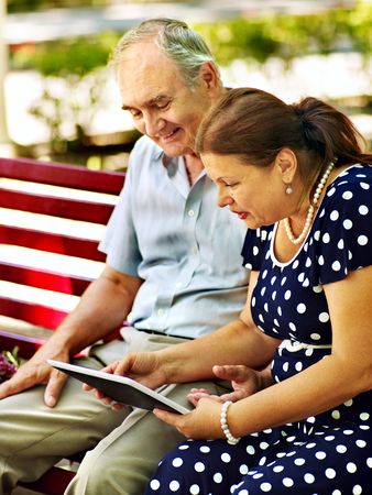 Old couple with tablet pc sit on bench  . Outdoor. photo