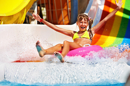 Happy child girl in yellow bikini sliding water park. photo