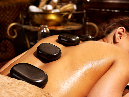 window treatments: Young woman having Ayurveda stone massage.