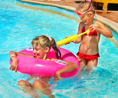 one piece: Children sitting on inflatable ring in swimming pool. Stock Photo