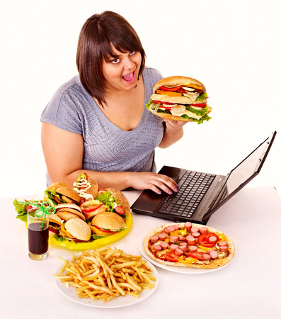 high calorie: Woman eating fast food at work. Isolated. Stock Photo
