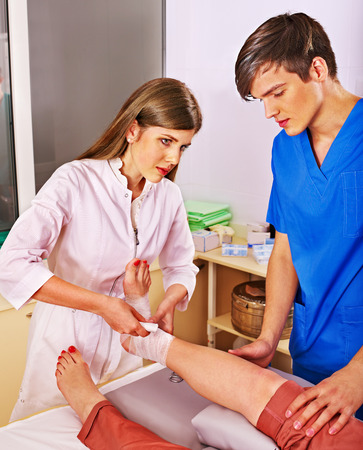 bandage wound: Doctor bandaging foot patient in hospital.