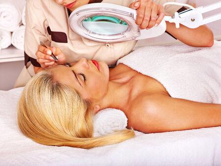 tweezing: Woman getting tweezing eyebrow by beautician.