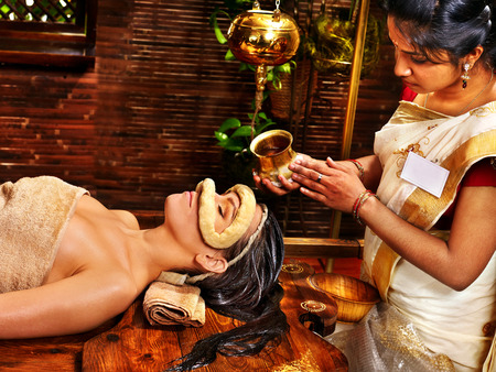 beautiful indian girl face: Woman having facial oil eyes mask at ayurveda spa.