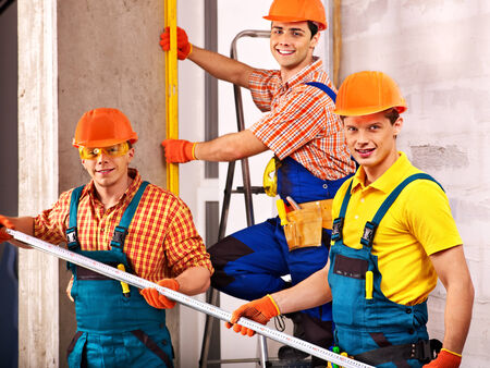 Happy group men in builder uniform indoor. photo