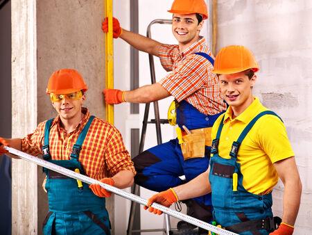 home remodel: Happy group men in builder uniform indoor.