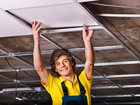 ceiling tile: Man in builder uniform installing suspended ceiling