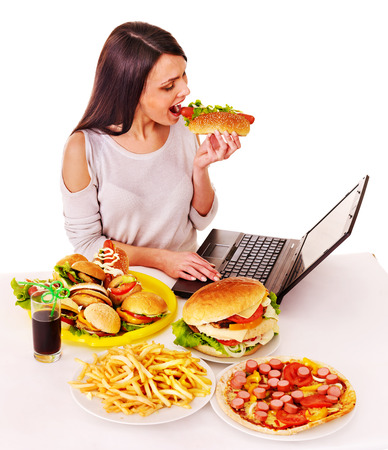 eat out: Woman eating fast food at work. Isolated. Stock Photo