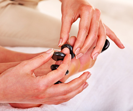 Woman receiving hot stone massage on feet. Stock Photo
