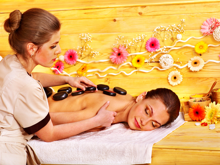 Happy woman getting stone therapy massage in spa. photo