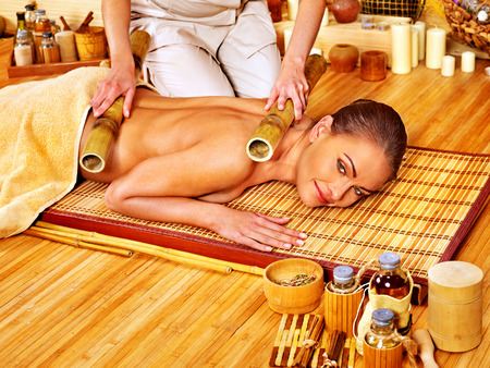 bamboo therapy: Young woman getting bamboo massage. Stock Photo
