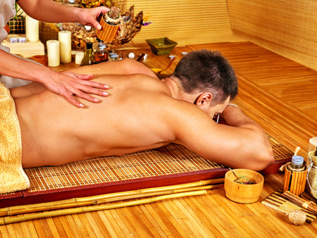 Man getting aroma massage in bamboo spa. photo