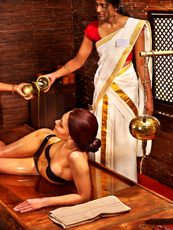 natural therapy: Young woman having oil Ayurveda spa treatment. Stock Photo
