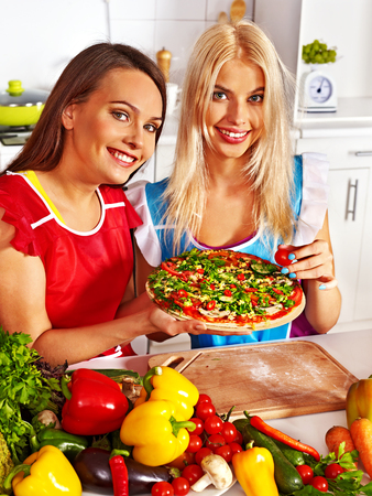 Women cooking pizza at kitchen. Stock Photo - 29945611