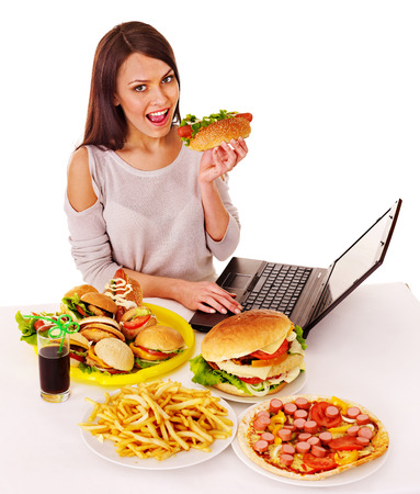 beefburger: Woman eating fast food at work. Isolated. Stock Photo