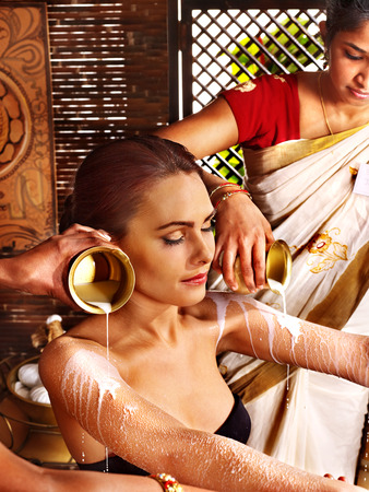 Woman having Ayurvedic spa treatment. Pouring milk. Stock Photo - 30617807