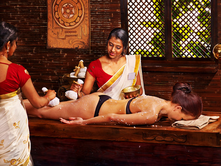Woman having Ayurveda massage with pouch of rice. Stock Photo - 30617811