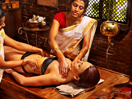 Young woman having stomach Ayurveda spa treatment. Stock Photo
