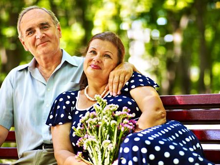 Old woman sit in hand of senior man. Outdoor. photo