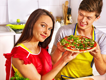 Young happy family cooking pizza at kitchen. photo