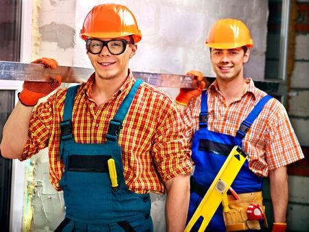 Happy group people men in builder uniform indoor. photo