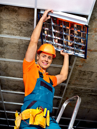 Man in builder uniform installing suspended ceiling photo