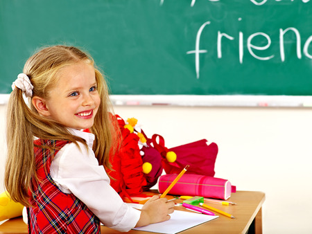 uniforms: Child holding school cone in classroom.