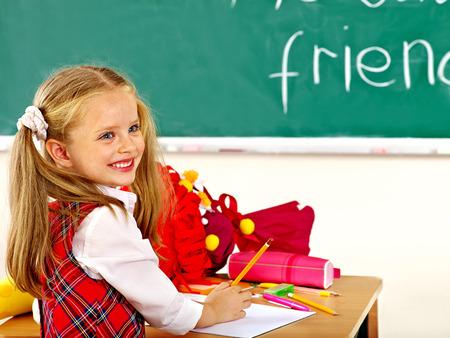school girl uniform: Child holding school cone in classroom.