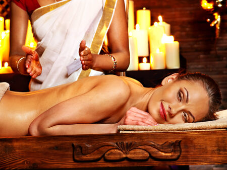 body oil: Young woman having oil Ayurveda spa treatment. Stock Photo