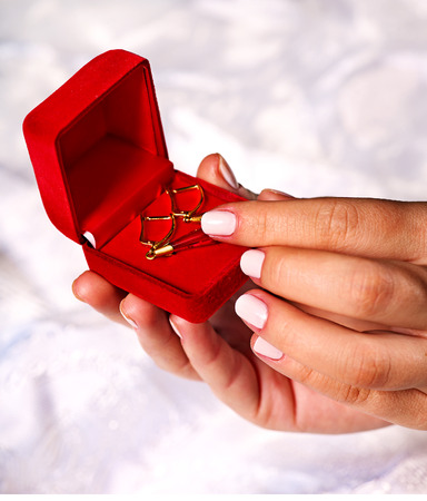 precious metal: Female hand holding jewelry box with earrings.Wedding background.