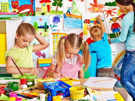 Happy children  with teacher painting. photo