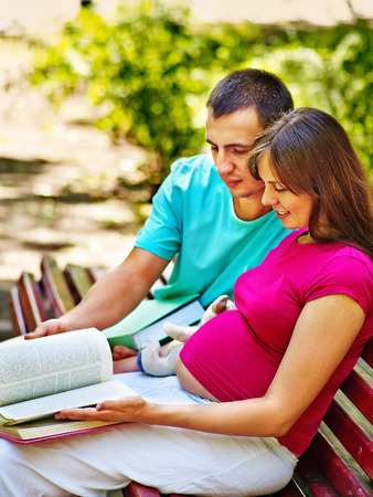Pregnant woman, reading book with man  outdoor in park. photo