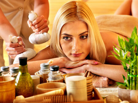 bamboo therapy: Blond woman getting herbal ball massage in spa.