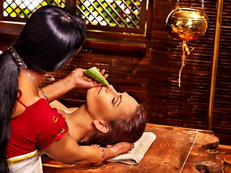 Woman having nose ayurveda spa treatment.